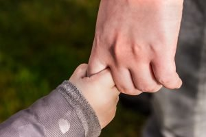 Photo of adult holding child's hand
